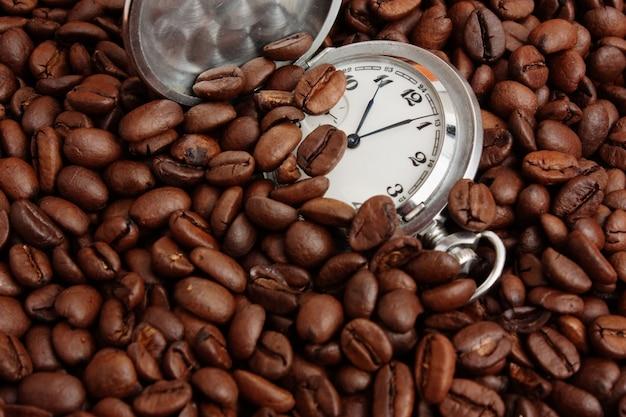 Zegarek kieszonkowy w kupie ziarna kawy