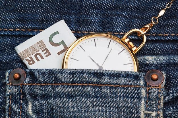 Zegarek kieszonkowy z łańcuchem w dżinsach i pięcioma euro. zbliżenie.