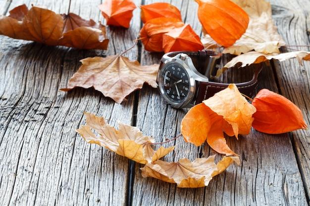 Zegarek na rękę na drewnianym stole z liści jesienią
