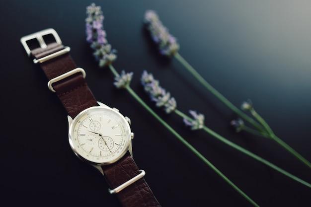 Zegarek na rękę na skórzanym pasku z gałązkami lawendy na czarnym tle.