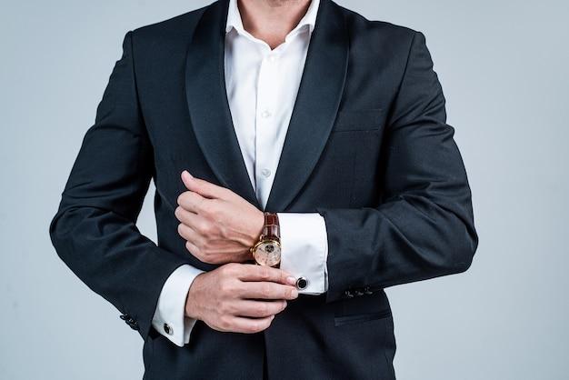 Zegarek na rękę noszony na męskim nadgarstku w formalnym smokingu szarym tle, zegarek.