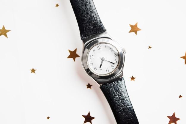 Zegarek na rękę z czarnym skórzanym paskiem i złotymi gwiazdami