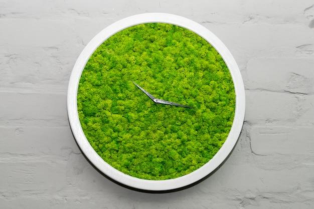 Zegarek naścienny z zielonym mchem na szarym ceglanym tle