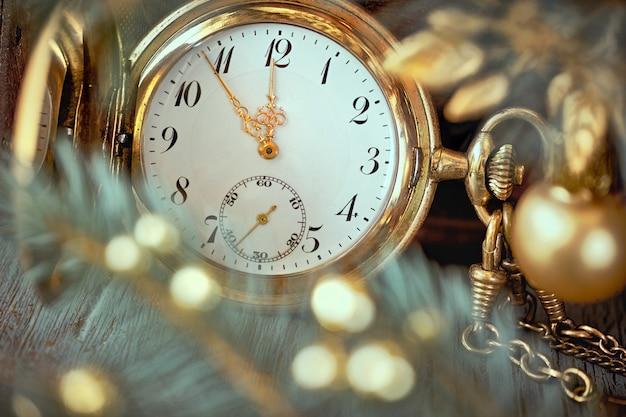Zegarek w stylu vintage przedstawiający pięć do dwunastu na szarym rustykalnym z gałązkami jodły i złotymi dekoracjami