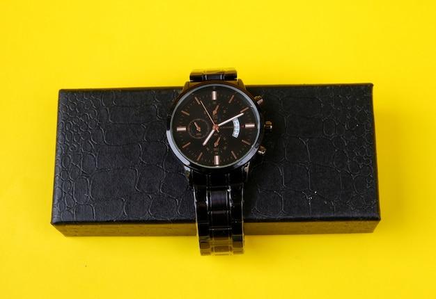 Zegarek z czarnym kartonem na żółtym tle