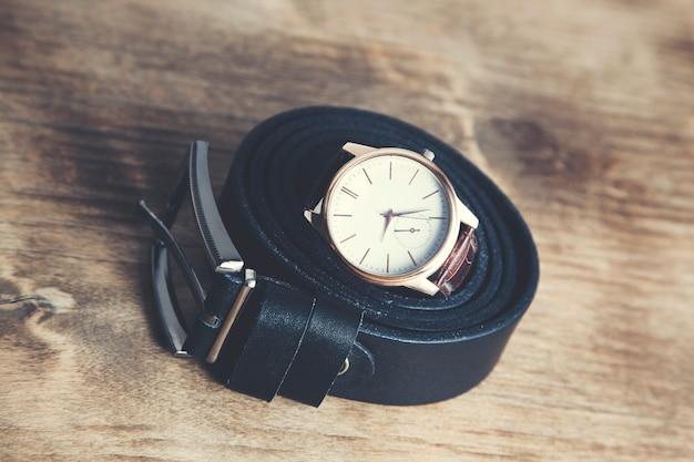 Zegarki i pasek na drewnianym tle
