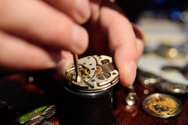 Zegarmistrz naprawia mechanizm zegarowy