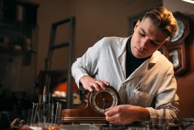 Zegarmistrz odnawia stary drewniany zegar stołowy
