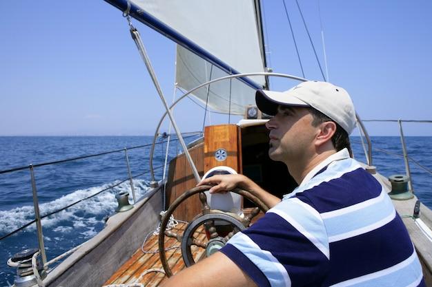 Żeglarz żeglujący po morzu. żaglówka na niebiesko