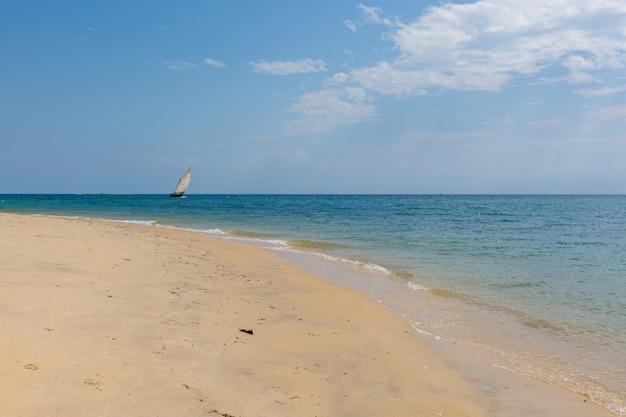 Żeglowanie łódź na spokojnym oceanie piaskowatą plażą chwytającą w zanzibar, afryka