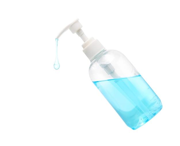Żel alkoholowy kapie z butelki na białej powierzchni