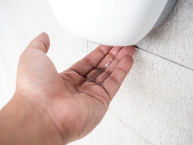 Żel alkoholowy w dłoni z białego automatycznego żelu dezynfekującego do rąk na ścianie