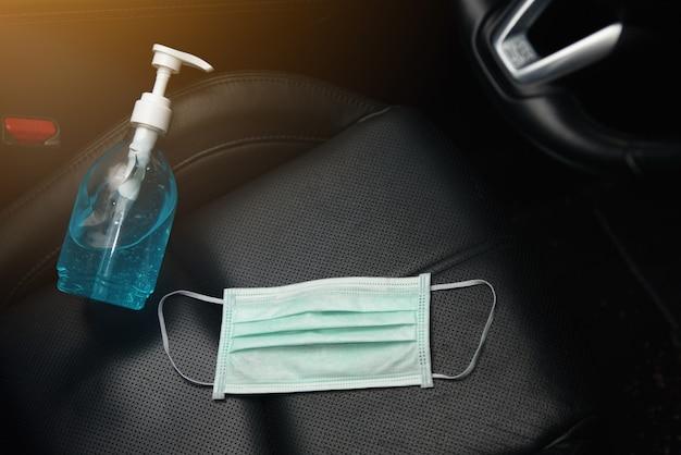 Żel do rąk z alkoholem etylowym i chirurgiczna maska na twarz umieszczona na foteliku samochodowym, koncepcja na koronawirusa, covid19