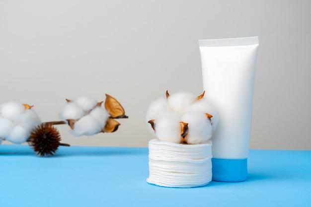 Żel oczyszczający i stos płatków kosmetycznych na tle papieru