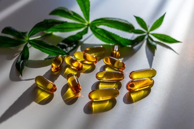 Żelatynowe kapsułki z siemienia lnianego i lnianego z zielonymi liśćmi. organiczny suplement diety. pojęcie opieki zdrowotnej i medycyny alternatywnej: homeopatia i naturopatia.