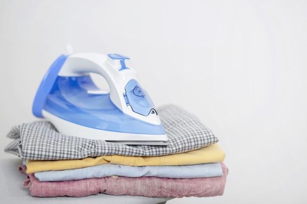 Żelazko elektryczne i stos czystej odzieży
