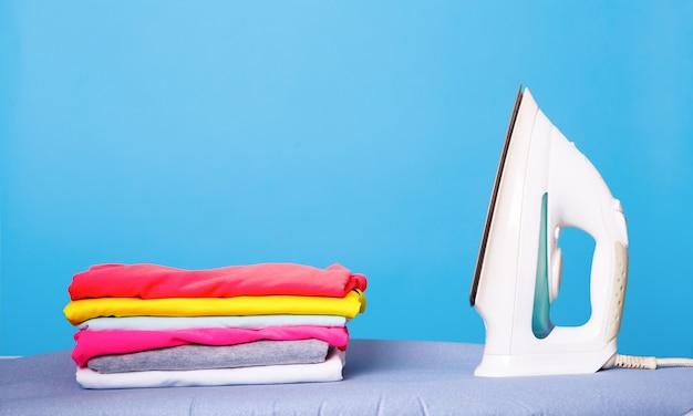 Żelazko elektryczne i stos ubrań na desce do prasowania. pojęcie prac domowych.