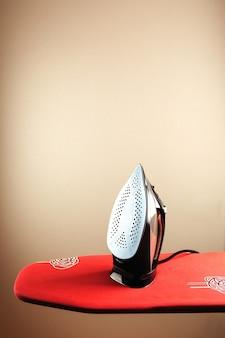 Żelazko elektryczne i stos ubrań na desce do prasowania