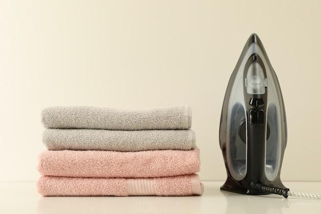 Żelazko i stos ręczników na białym tle
