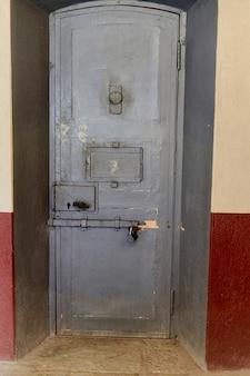 Żelazne drzwi do celi więziennej z oknem obserwacyjnym i stalowymi ryglami. metalowe drzwi więzienne