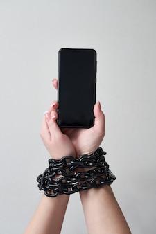 Żelazny łańcuch, który łączy rękę i smartfon w koncepcji mediów społecznościowych i uzależnienia od internetu na szarej ścianie
