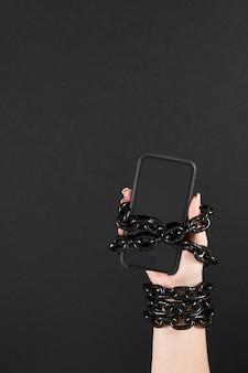 Żelazny łańcuch, który łączy rękę i smartfon w koncepcji uzależnienia od mediów społecznościowych i internetu