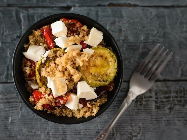 Żelazny widelec z sałatką z komosy ryżowej i warzywami z serem na czarnym stole. danie wegetariańskie. naturalna zdrowa żywność. widok z góry. leżał na płasko.