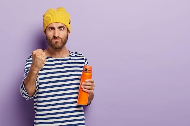 Zemszczę się! oburzony niezadowolony mężczyzna pokazuje pięści, patrzy ze złością, marszczy brwi, trzyma butelkę lub termos, ubrany w stylowy strój, wyraża negatywne emocje