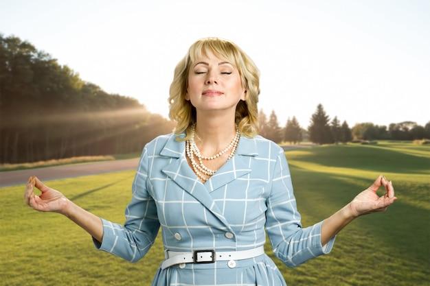 Zen relaks wspaniałej dojrzałej kobiety. blond kobieta w średnim wieku praktykuje medytację z zamkniętymi oczami na przyrodę.