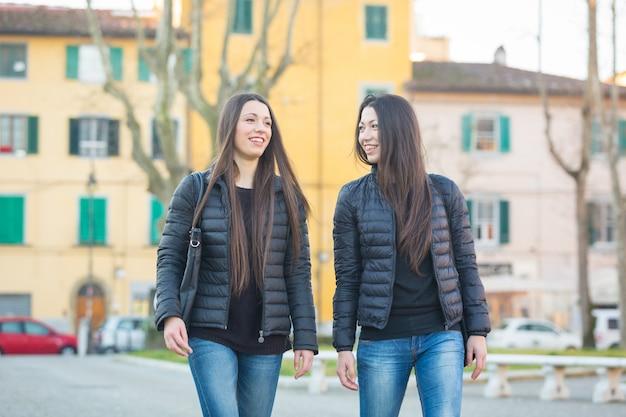 Żeńscy bliźniacy chodzi przy miasto placem publicznym