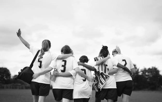 Żeńscy gracze futbolu skuleni i chodzący razem