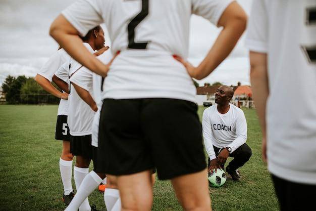 Żeńscy gracze futbolu słucha trener