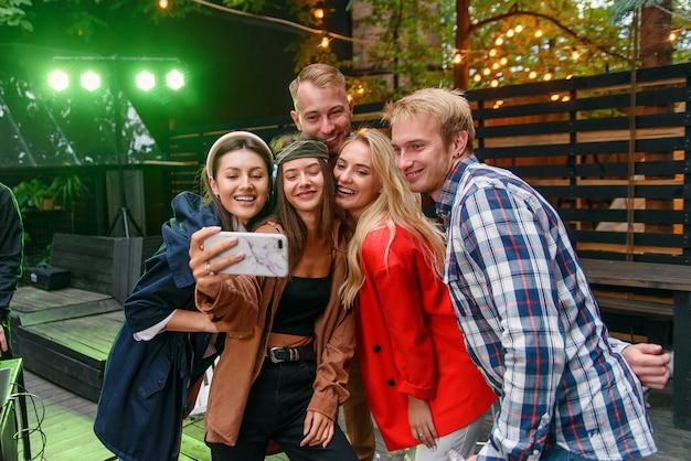 Żeńscy i męscy przyjaciele świętuje przyjęcie outdoors i bierze selfie fotografię na smartphone.