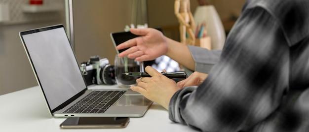 Żeńscy pracownicy konsultuje na ich pracie z egzaminu próbnego laptopem na bielu stole