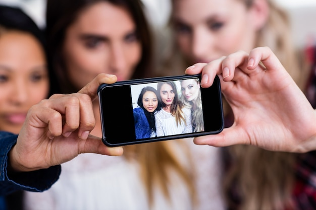 Żeńscy przyjaciele bierze selfie z telefonem komórkowym w domu