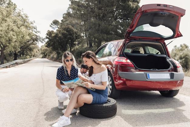 Żeńscy przyjaciele patrzeje mapy obsiadanie blisko łamanego puszka samochodu na drodze
