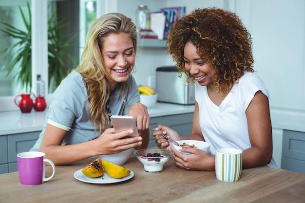Żeńscy przyjaciele patrzeje w telefonie komórkowym podczas śniadania