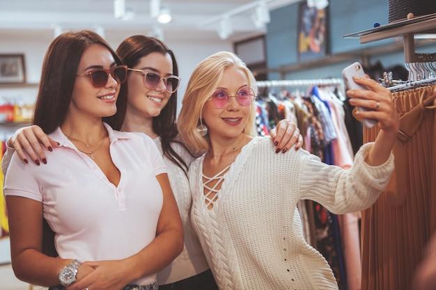 Żeńscy przyjaciele robi zakupy wpólnie w sklepie odzieżowym