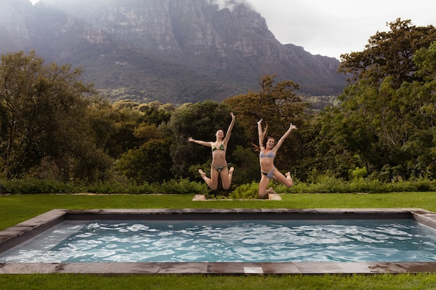 Żeńscy przyjaciele skacze w pływackim basenie przy podwórkiem