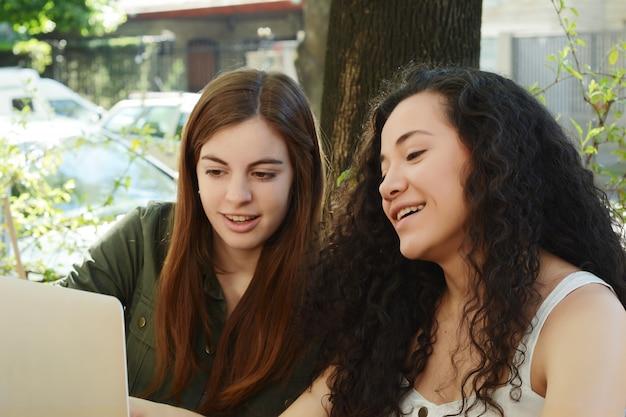 Żeńscy przyjaciele studiuje z laptopem w sklep z kawą.