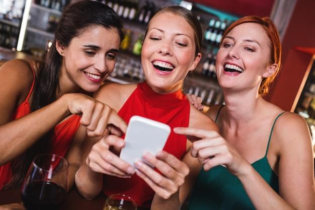 Żeńscy przyjaciele używa telefon komórkowego podczas gdy cieszący się wino