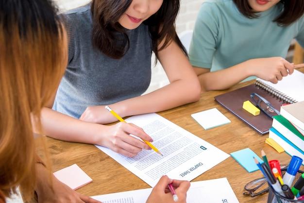 Żeńscy studenci collegu robi przydziałowi przy stołem