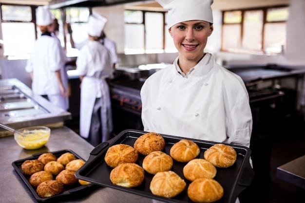 Żeńscy szefowie kuchni trzyma wypiekową tacę kaiser rolki w kuchni