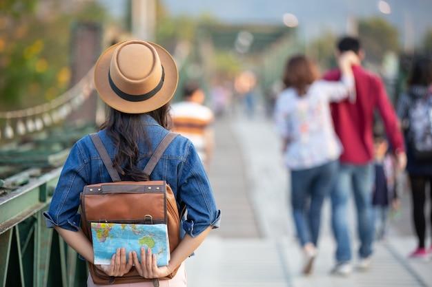 Żeńscy turyści na ręce mają szczęśliwą podróż mapę.