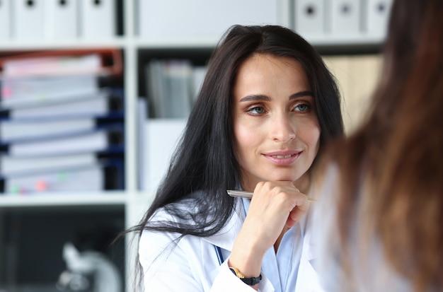 Żeńska caucasian lekarka słucha pacjenta w medycyna szpitalu