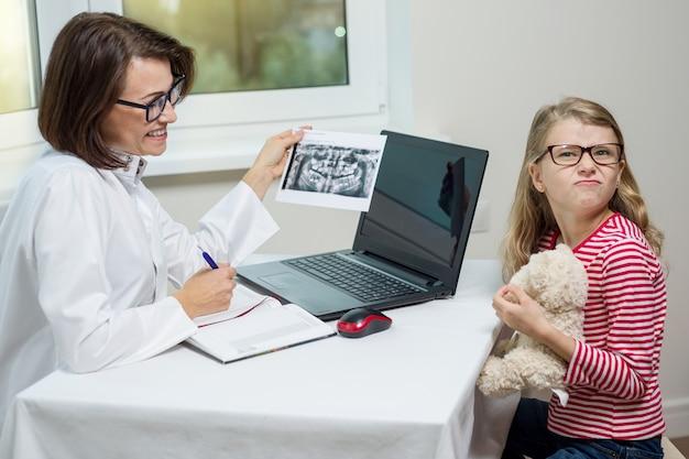 Żeńska dentysty ortodonta opowiada z dzieckiem z promieniowaniem rentgenowskim.