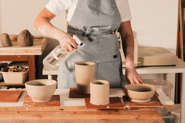Żeńska garncarka rozpyla ciecz na handmade glinianych pucharach i słoju na drewnianym stole