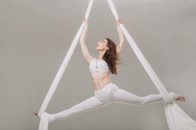 Żeńska gimnastyczka robi powietrznym jedwabniczym akrobacjom