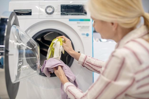 Żeńska gospodyni wkłada ubrania do pralki