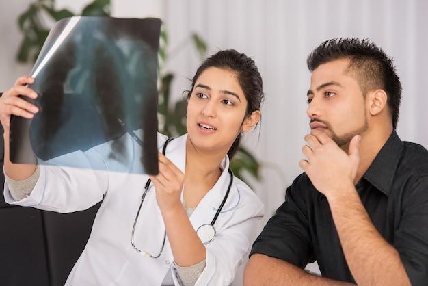 Żeńska indiańska lekarz komunikacja z męskimi pacjentami.